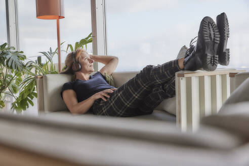 Woman with hand in hair listening music while lying on sofa at home - FMKF06989