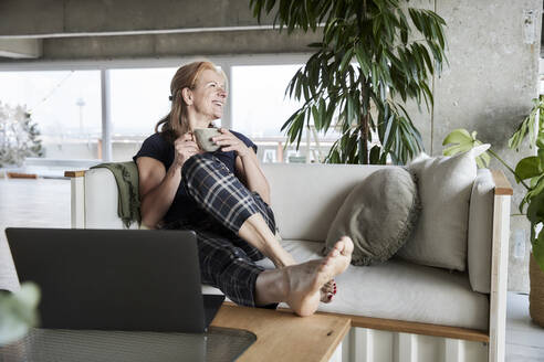 Smiling woman with laptop holding coffee cup while sitting on sofa at home - FMKF06992