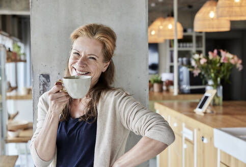 Happy mature woman with hand on hip having coffee against column at home - FMKF06995