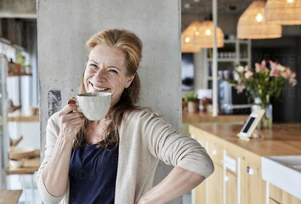 Glückliche reife Frau mit Hand auf der Hüfte mit Kaffee gegen Spalte zu Hause - FMKF06995 - Jo Kirchherr/Westend61