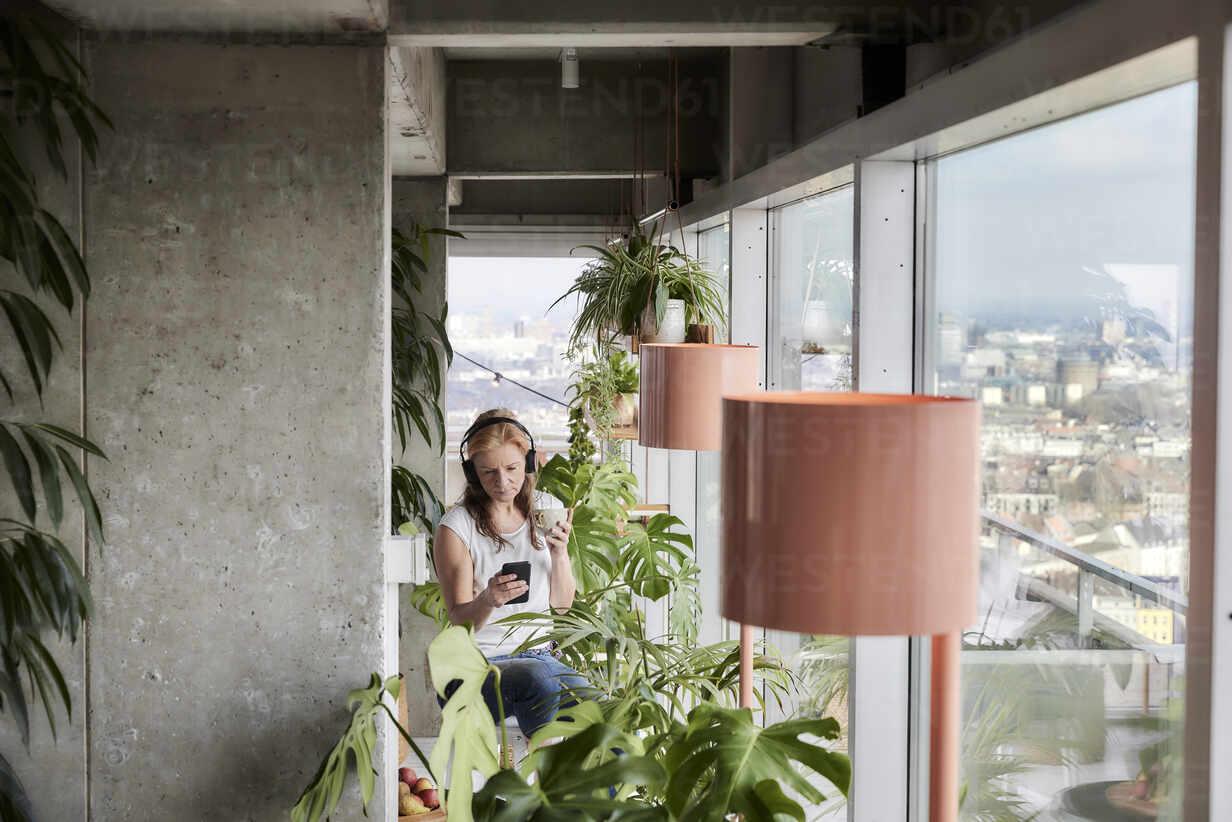 Frau mit Kaffeetasse mit Handy beim Sitzen auf Balkon zu Hause - FMKF06998 - Jo Kirchherr/Westend61