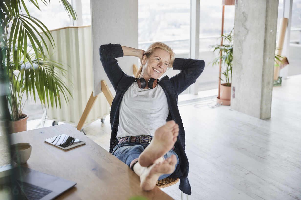 Lächelnde Geschäftsfrau mit Händen hinter dem Kopf sitzt auf einem Stuhl und schaut weg - FMKF07007 - Jo Kirchherr/Westend61