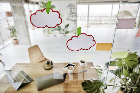 Adhesive notes sticked on glass wall in office - FMKF07016