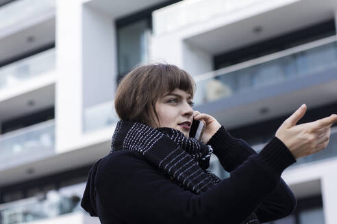 Woman gesturing while talking on mobile phone standing against building - SGF02766