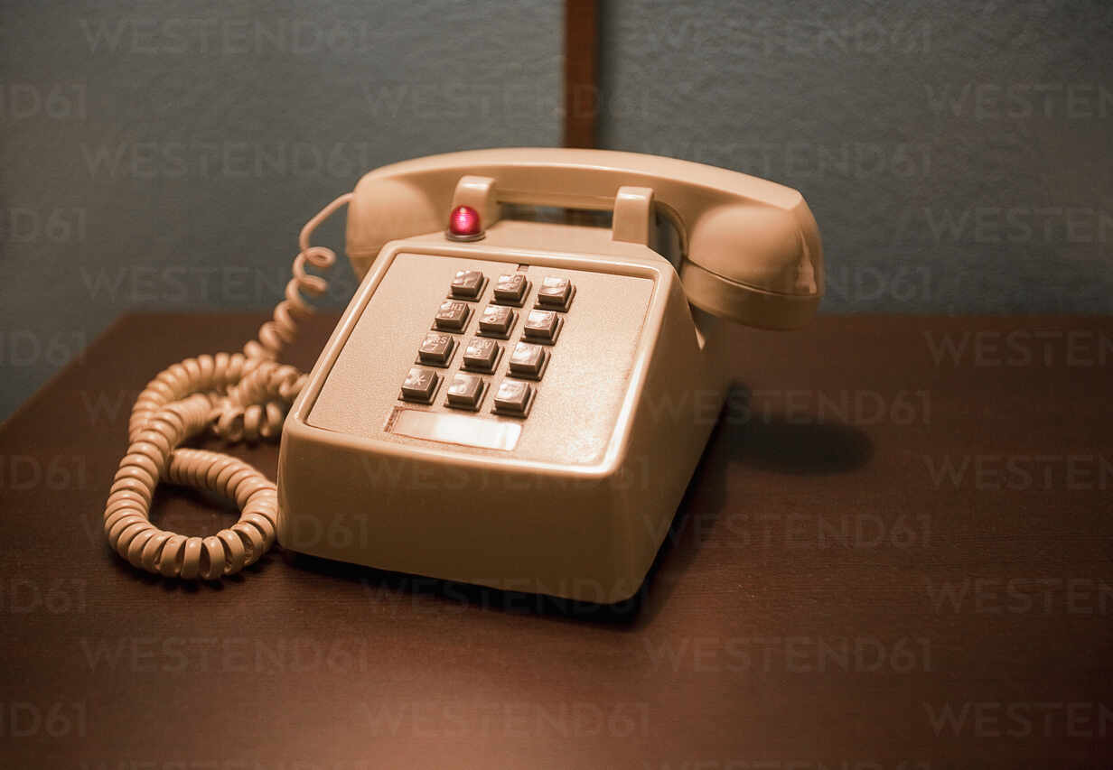Pfirsich Farbe Telefon auf Holztisch - AJOF01079 - LOUIS CHRISTIAN/Westend61