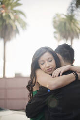 Young man and woman (23-30) embracing outdoors, Los Angeles, USA - AJOF01085