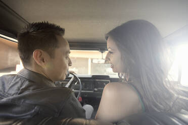 Young man and woman (23-30) chatting in car, Los Angeles, USA - AJOF01088