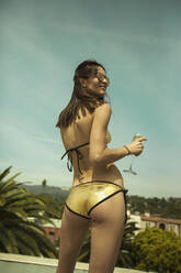 Young woman (23-30) in bikini, holding glass of Champagne, Los Angeles, California, USA - AJOF01090
