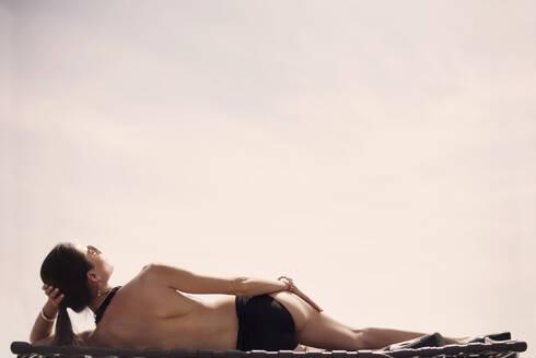 Young woman in bikini sunbathing while lying against sky - AJOF01099