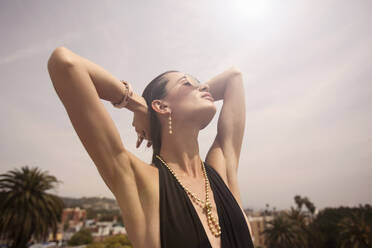 Young woman (23-30) in swimsuit, face turned to the sun, Los Angeles, California, USA - AJOF01105