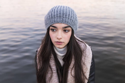 Thoughtful teenage girl against river during sunset - JRVF00287