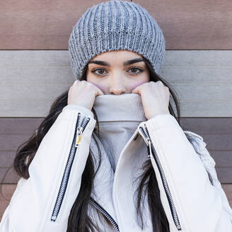 Beautiful teenage girl in knit hat covering her mouth with sweater against wall - JRVF00302