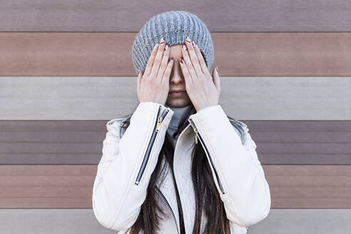 Teenage girl covering her face with hands while standing against wall - JRVF00305