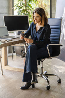 Smiling female entrepreneur using smart phone while sitting on chair in office - DLTSF01622