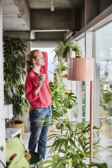Woman with eyes closed holding coffee cup while standing amidst plants at home - FMKF07045