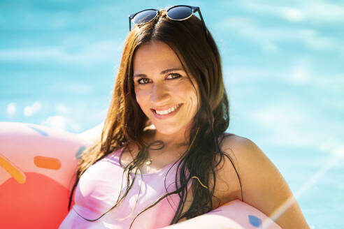 Happy beautiful woman with inflatable ring floating on water in swimming pool during sunny day - AKLF00081