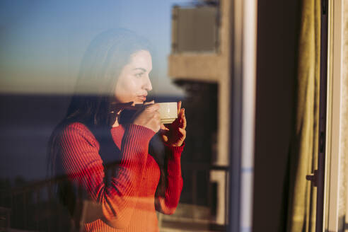 Woman having coffee while looking through window at home - LJF02077