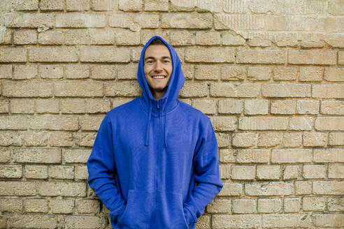 Smiling male athlete in blue jacket against brick wall - KVF00190