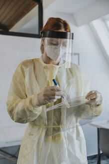 Female doctor wearing protective workwear putting sample in plastic bag while standing at examination room - MFF07407