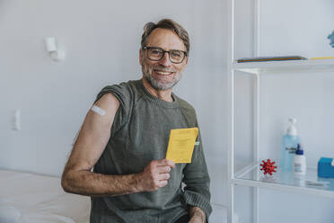 Smiling man with bandage on arm showing vaccination certificate while sitting at examination room - MFF07440