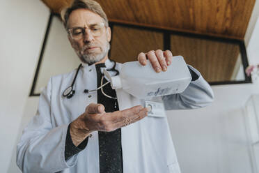 Mature doctor using hand sanitizer while standing at clinic - MFF07467