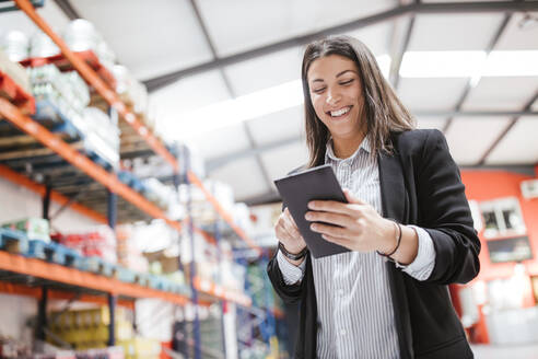 Smiling female manager using digital tablet in illuminated distribution warehouse - LJF02089