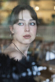 Beautiful woman with blue eyes looking through window at cafe - PNAF00862
