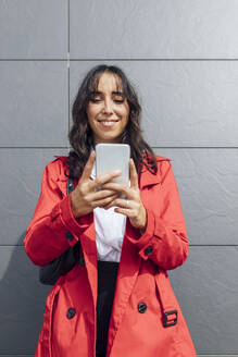 Smiling young businesswoman using phone while standing against gray color wall - JRVF00317