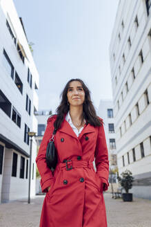 Smiling businesswoman with hands in pockets walking on footpath - JRVF00338