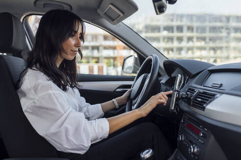 Young woman setting up global positioning system through smart phone while sitting in car - JRVF00341