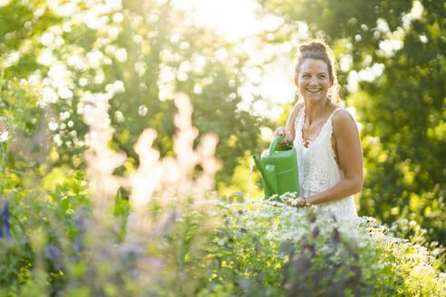Deutschland, Hessen, Wiesbaden, Frau gießt Blumen im eigenen Garten, Natur, Nachhaltigkeit, Gießkanne, Pflanzen, Draußen im Grünen - AKLF00106